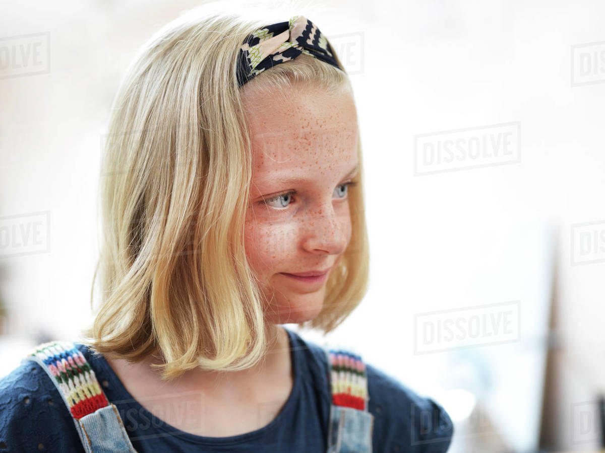 Girl with freckles and blond bobbed hair looking away, head and shoulder portrait Royalty-free stock photo