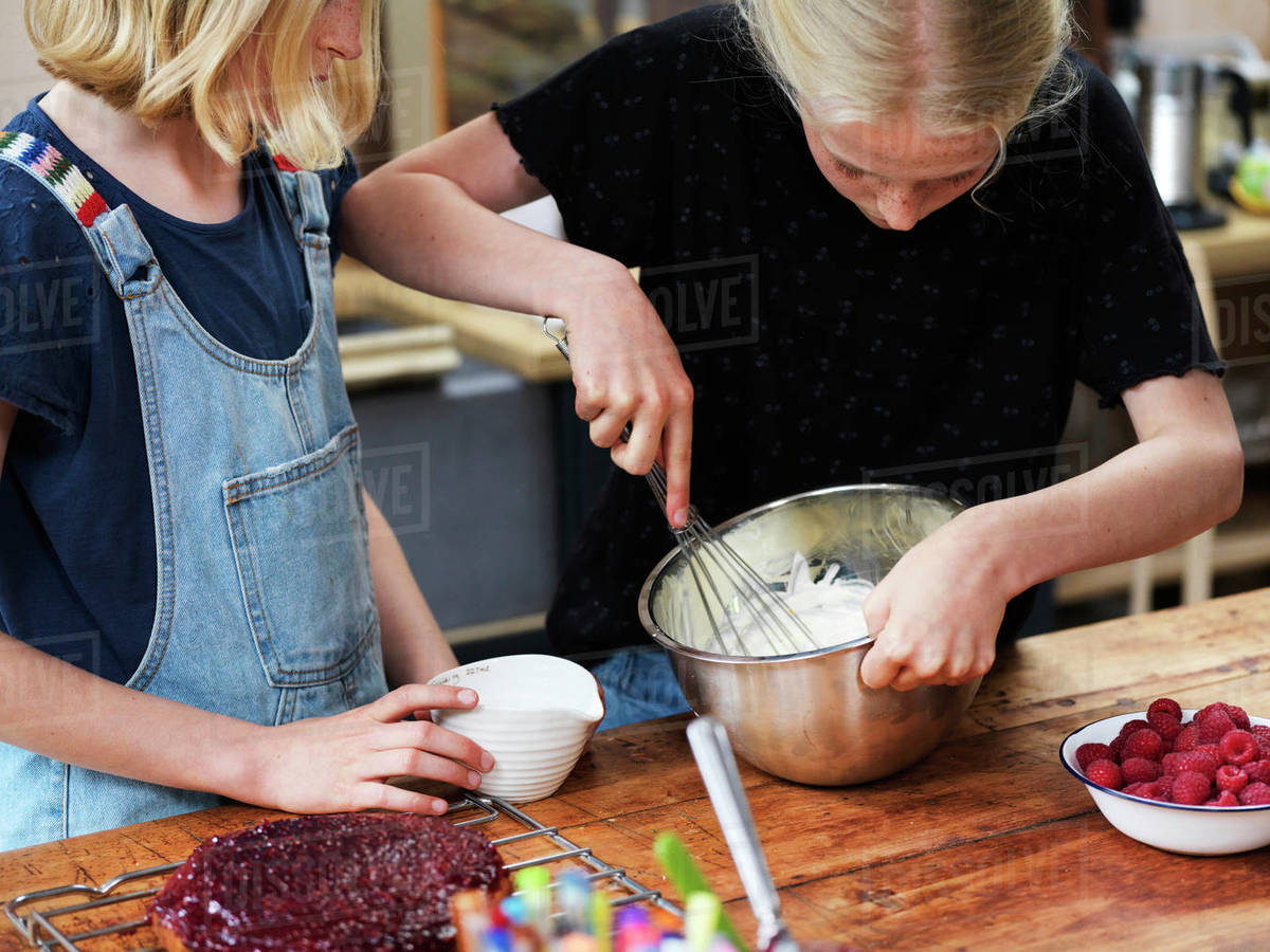 Girl and her sister baking a cake, whisking cream in mixing bowl at kitchen table Royalty-free stock photo