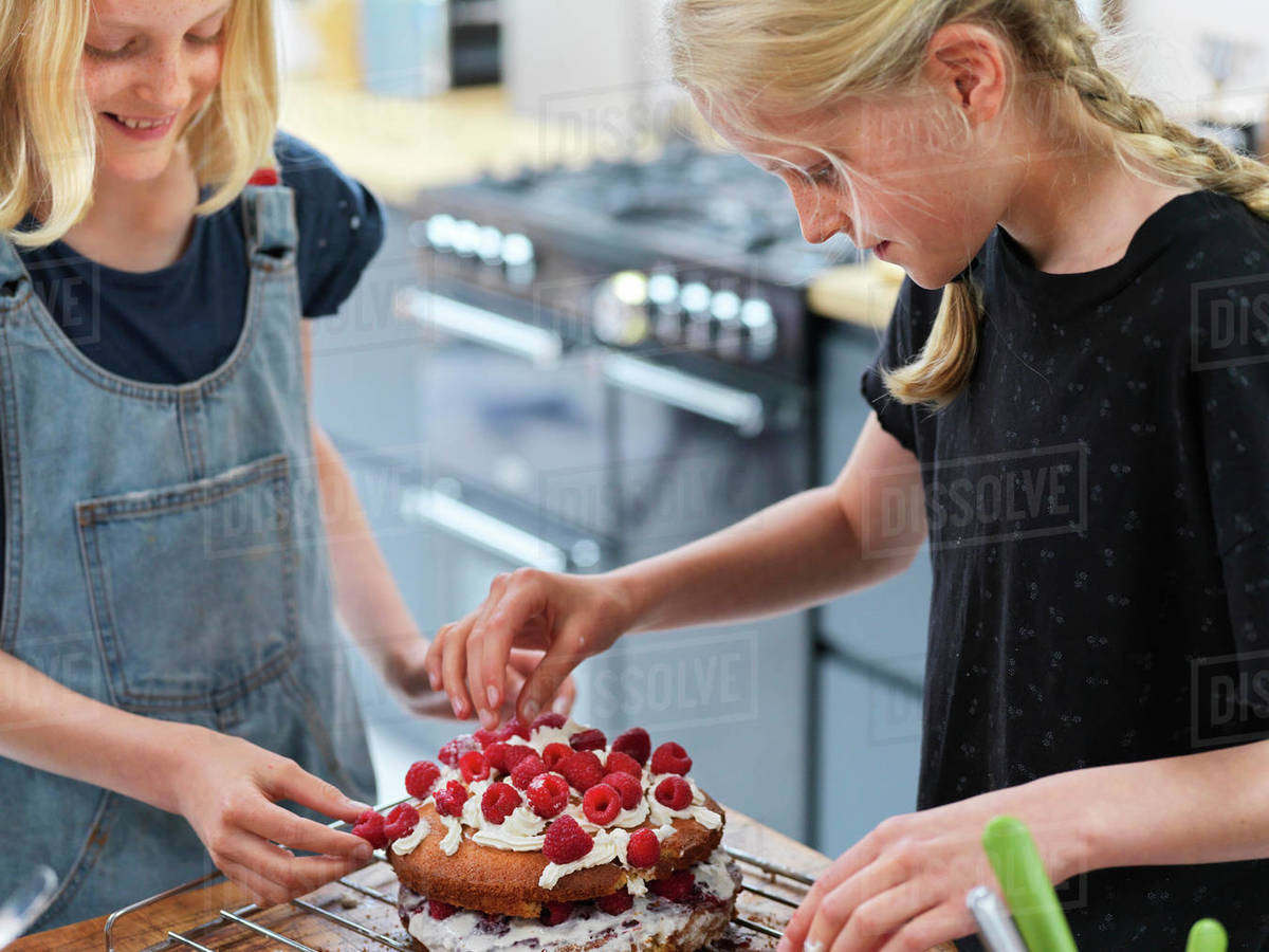 Girl and her sister baking a cake, decorating cake with fresh cream and raspberries at kitchen table Royalty-free stock photo