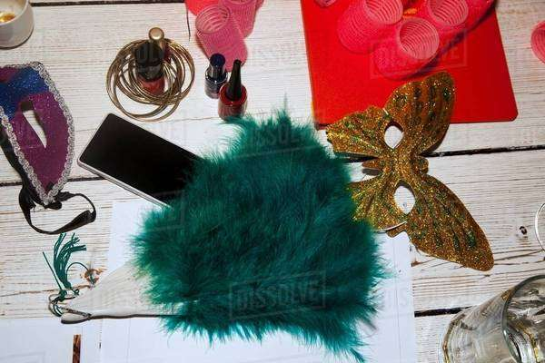 Feather fan, party mask, hair rollers, nail varnish, smartphone Royalty-free stock photo