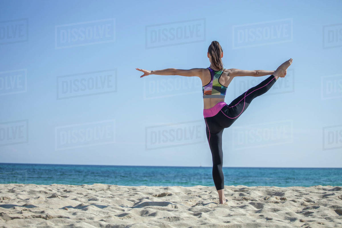 Rear view of woman standing on a sandy beach, doing yoga. Royalty-free stock photo