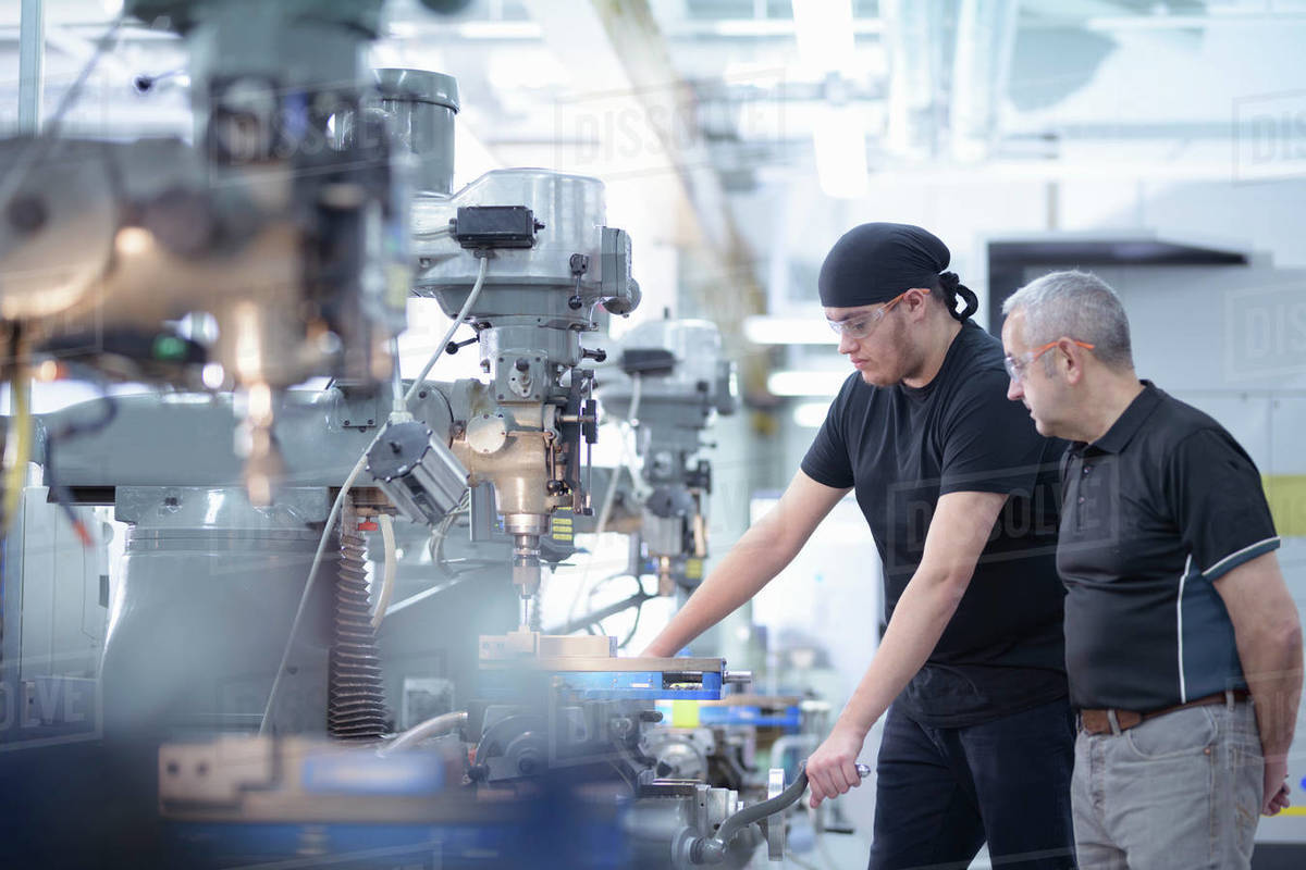 Two male engineers standing next to drills in engineering factory. Royalty-free stock photo