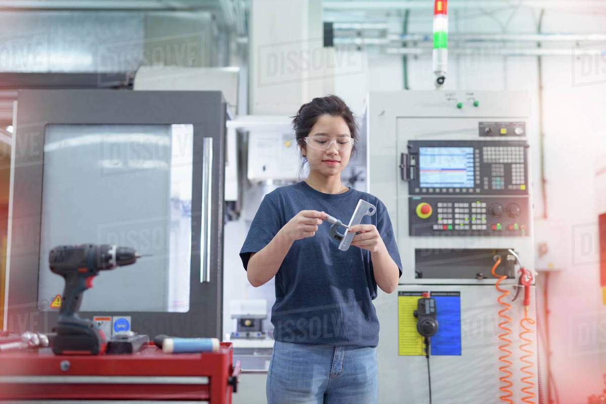 Female engineer standing next to CNC lathe in factory. Royalty-free stock photo