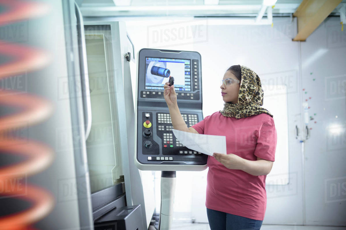 Female engineer inspecting CNC lathe in factory. Royalty-free stock photo
