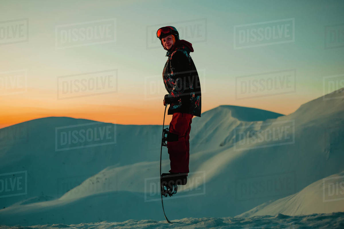 A man wearing a ski suit, helmet and goggles on a snowy mountain ridge at sunset Royalty-free stock photo