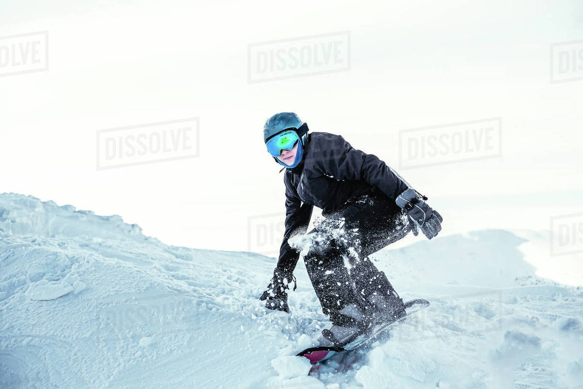 A snowboarder crouched on a ridge of snow ready to push off Royalty-free stock photo