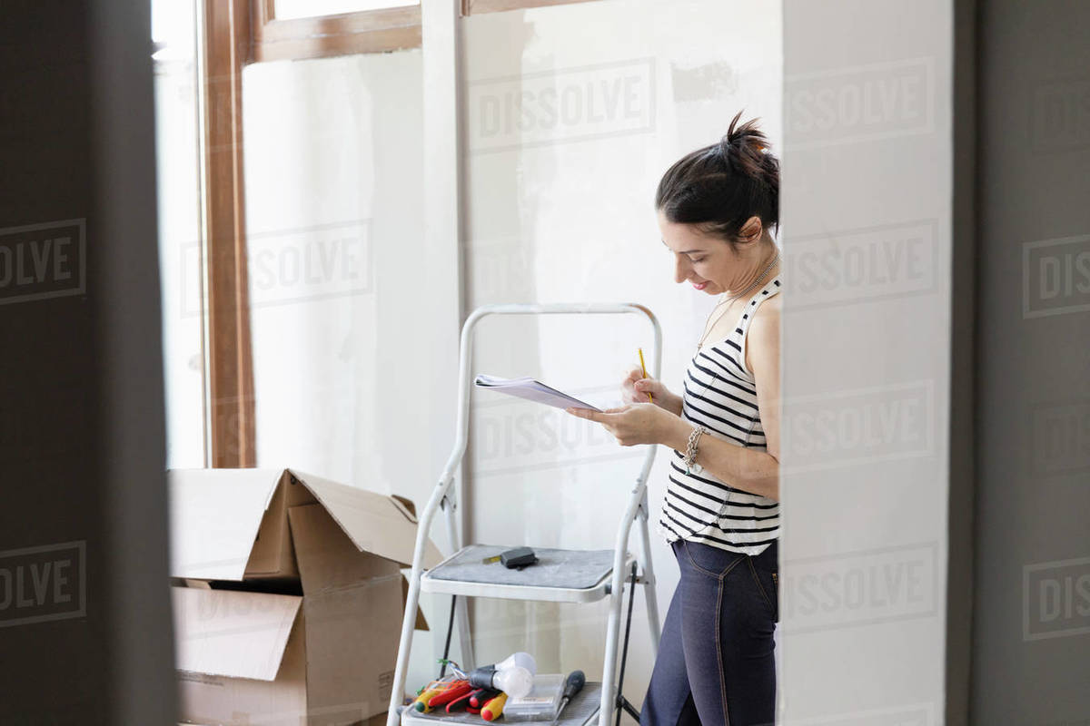 Woman looking at a pad of paper standing next to a stepladder and cardboard boxes. Royalty-free stock photo