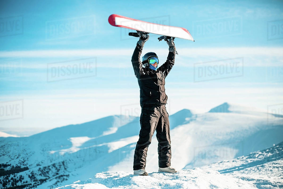 A person wearing a black ski suit, helmet and goggles on top of a mountain holding a red snowboard above their head. Royalty-free stock photo