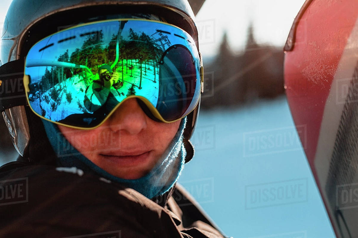 Head and shoulders of person wearing a black helmet and dark goggles on a ski slope. Royalty-free stock photo