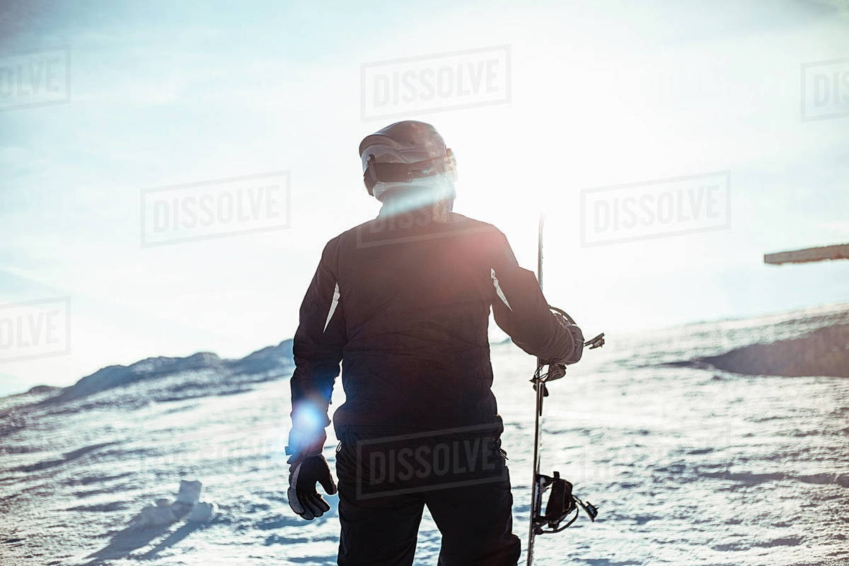 Silhouette of a person wearing a black ski suit, helmet and goggles holding a snowboard standing on top of a snowy slope. Royalty-free stock photo