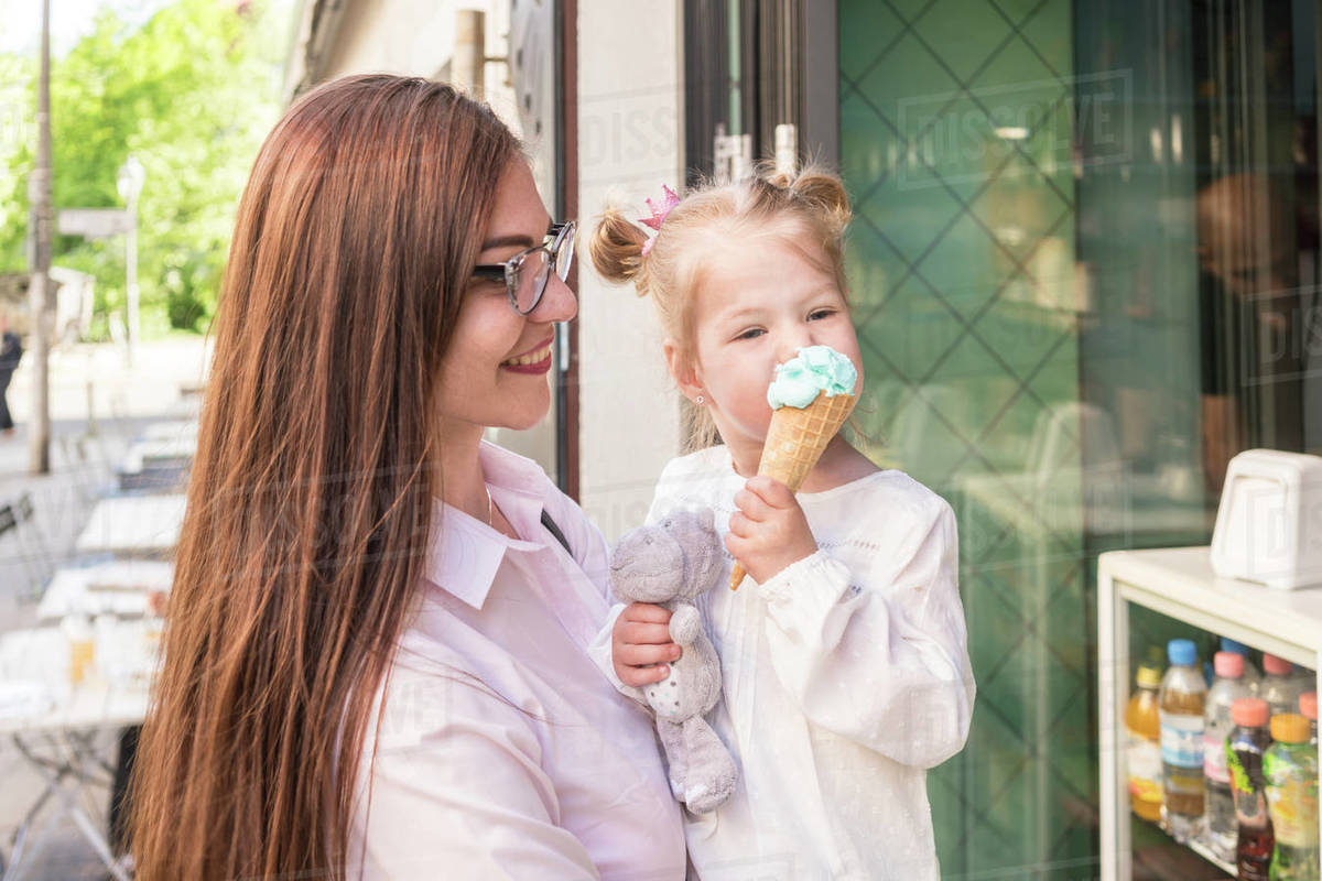 A mother standing outside a cafe holding her daughter as she eats an ice cream cone and holds a cuddly toy. Royalty-free stock photo