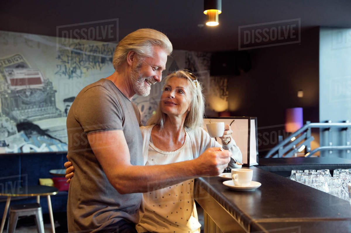 A couple standing together at a bar with cups of coffee. Royalty-free stock photo
