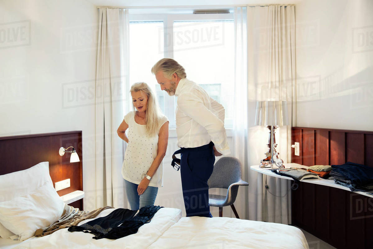 A couple standing in a hotel room looking at clothes laid out on the bed. Royalty-free stock photo