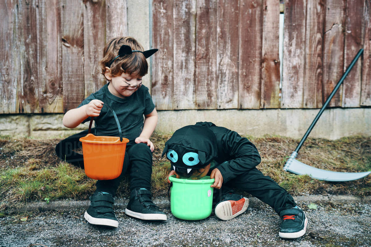 Two children dressed for Halloween sitting at the side of the road looking into their buckets of sweets. Royalty-free stock photo