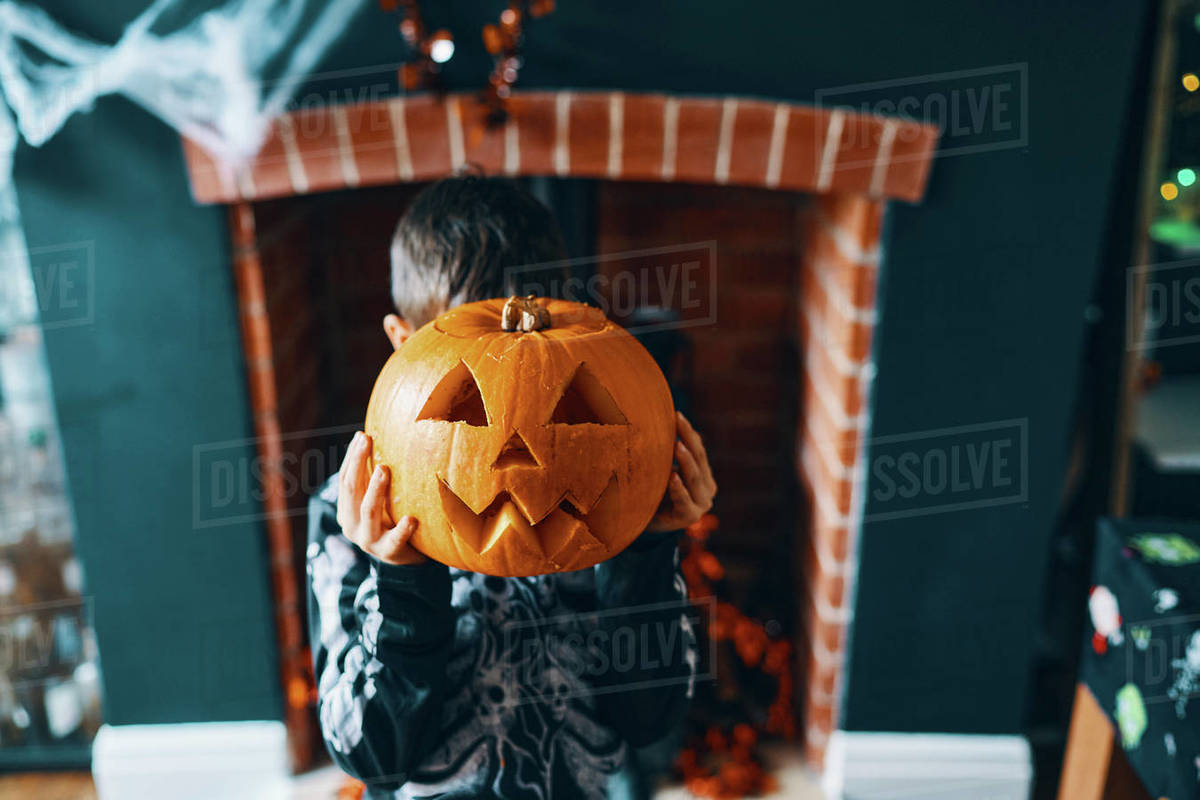 A boy holding a pumpkin head in front of his face. Royalty-free stock photo