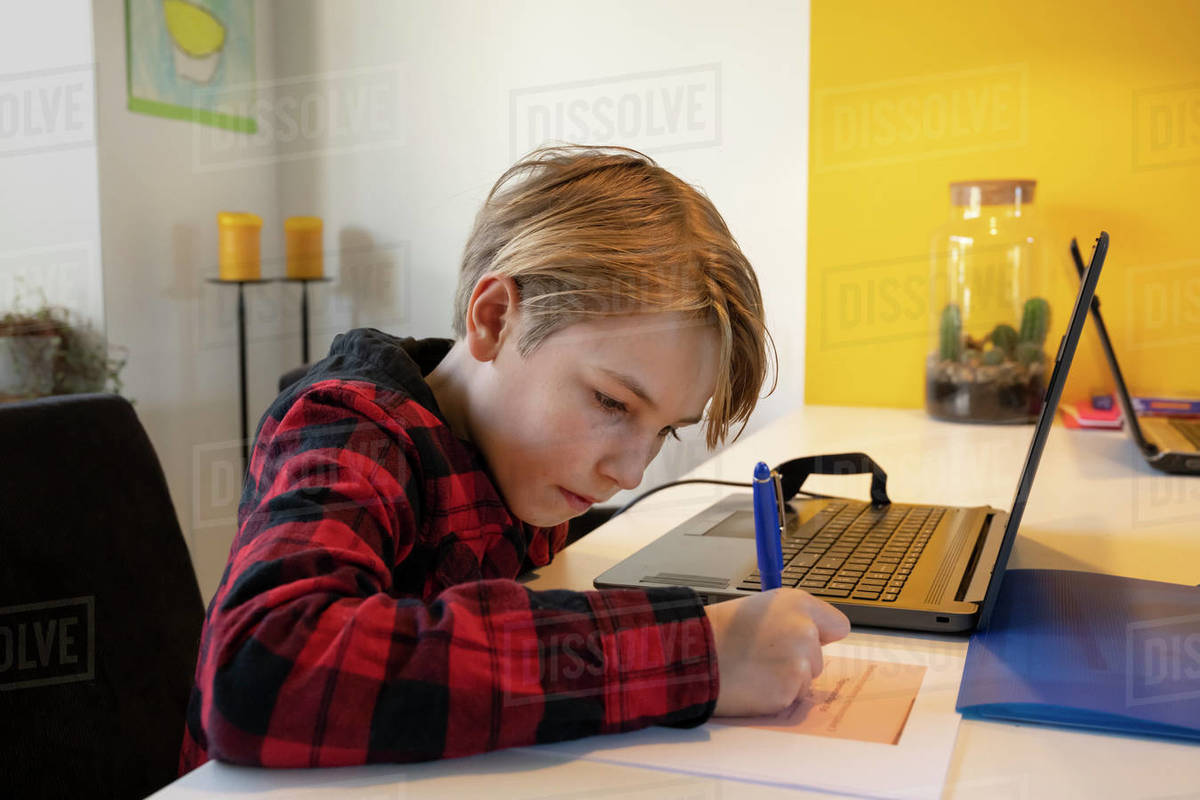 Boy indoors during Corona virus crisis, sitting at table with laptop computer, doing homework. Royalty-free stock photo