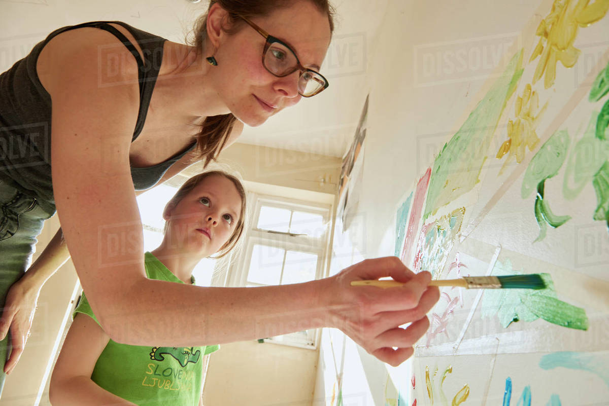 Smiling woman and girl indoors during Corona virus crisis, painting on a wall. Royalty-free stock photo