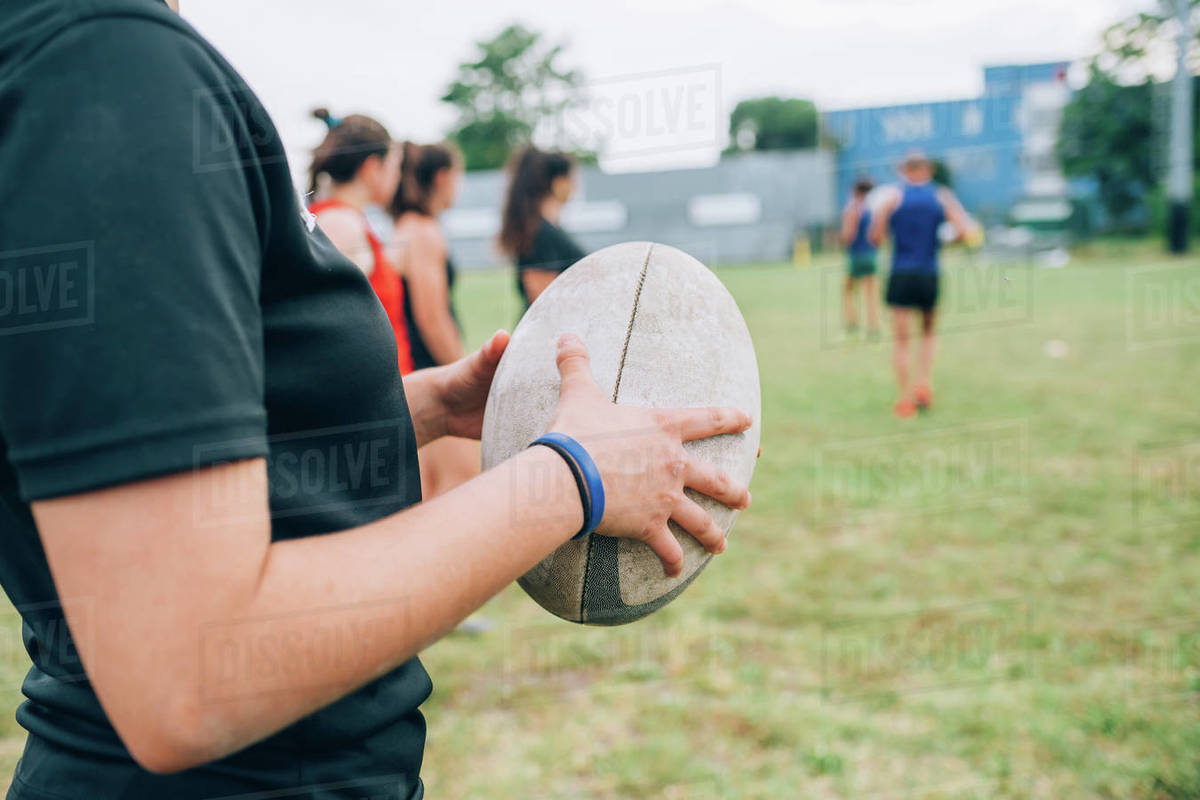 A group of women and their male coach at rugby training, one woman holding a rugby ball. Royalty-free stock photo