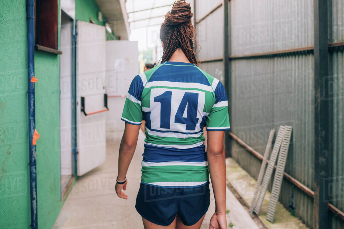 Rear view of a woman wearing a green, blue and white rugby shirt walking towards the dressing rooms. Royalty-free stock photo
