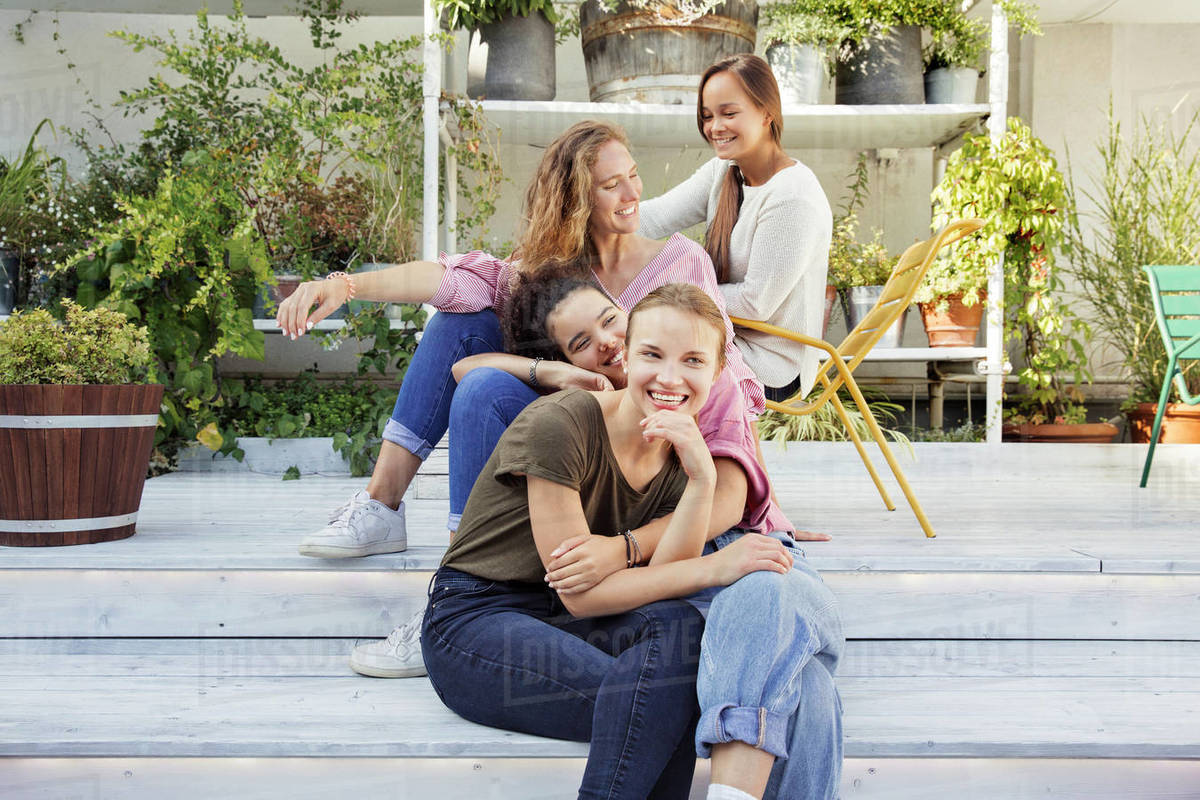 Four smiling women sitting in a courtyard with plants in the background. Royalty-free stock photo