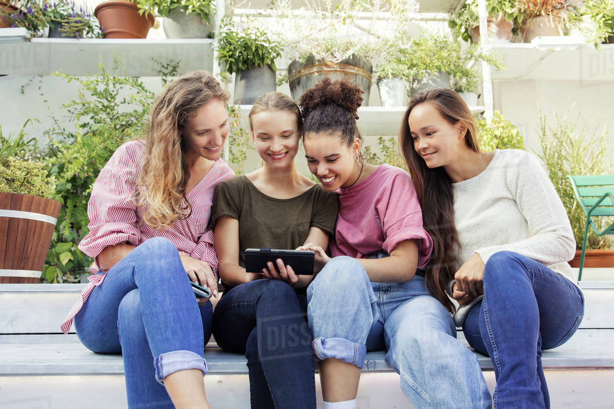 Four women sitting in a courtyard, looking at a phone and smiling. Royalty-free stock photo