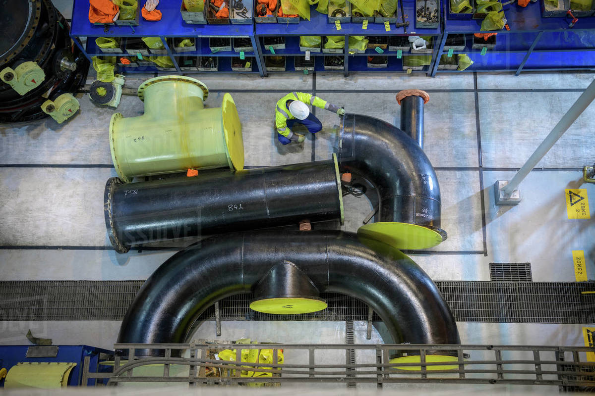 Overhead view of engineer inspecting pipes in a nuclear power station. Royalty-free stock photo