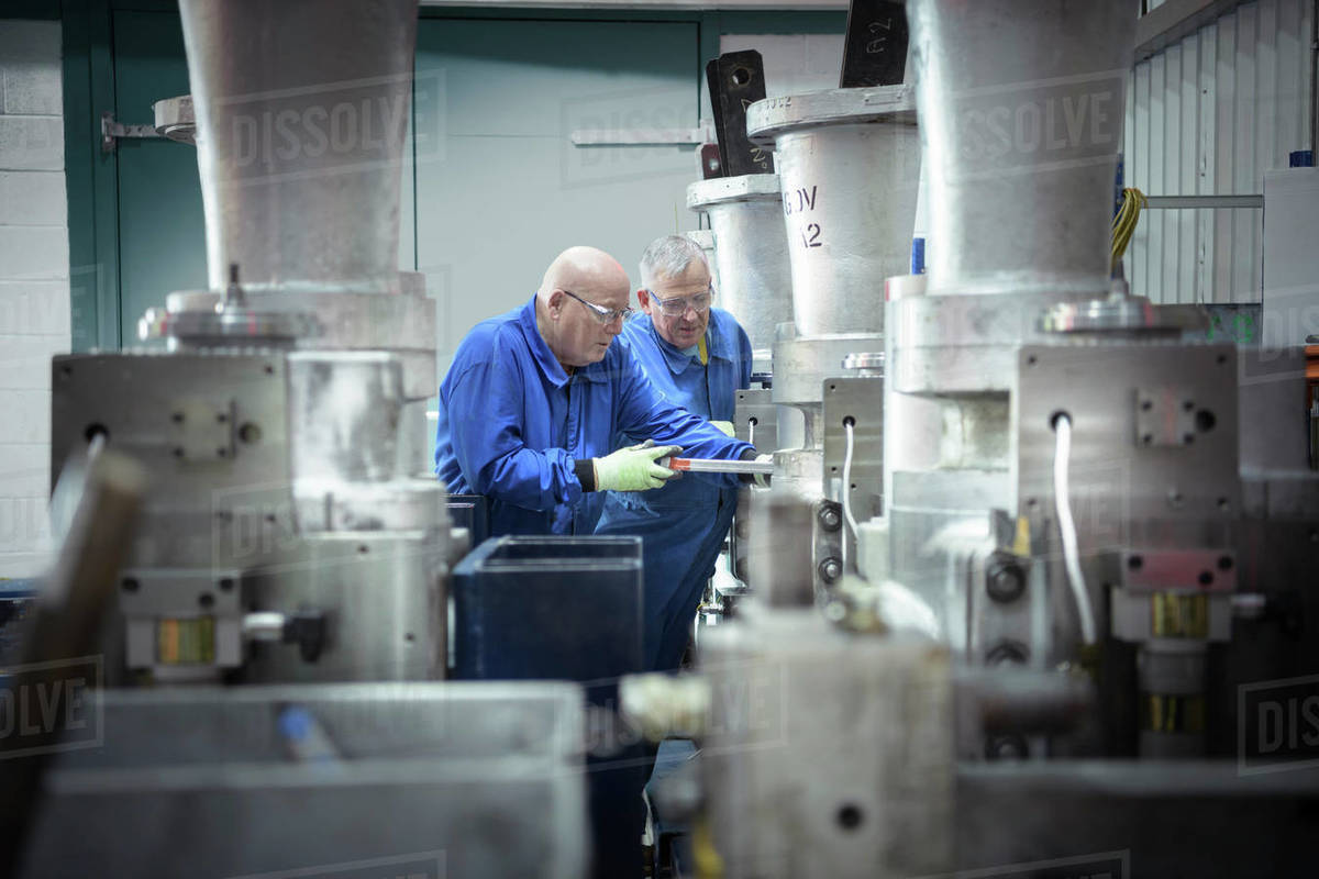 Two engineers inspecting a valve in a nuclear power station. Royalty-free stock photo