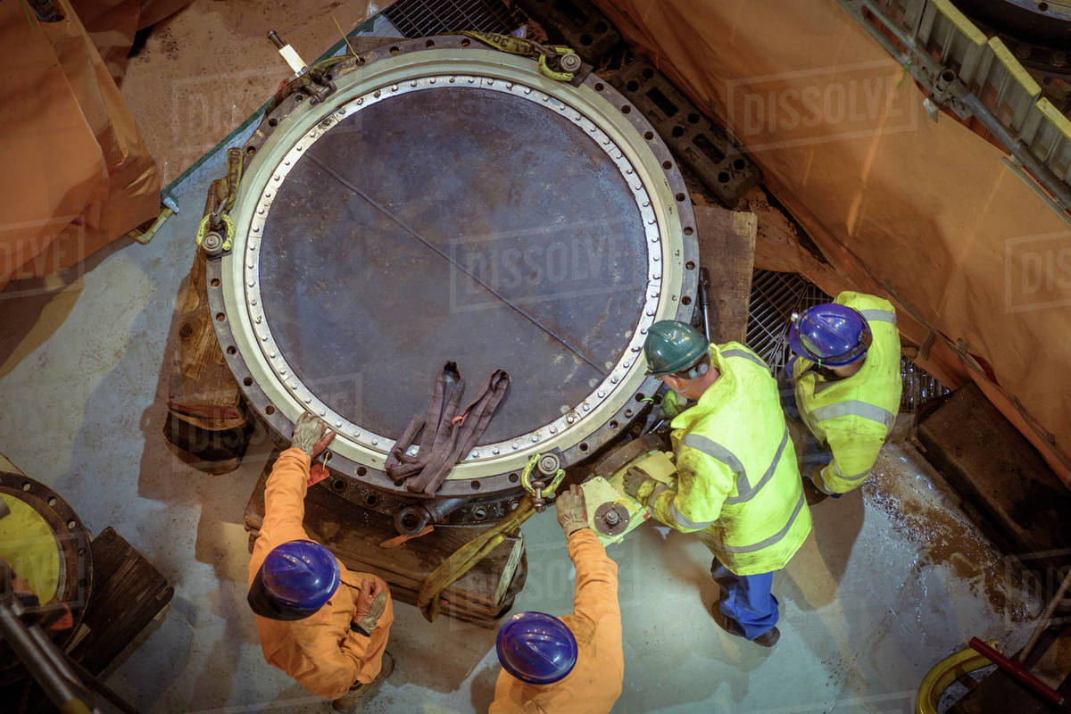 Overhead view of engineers inspecting a valve in a nuclear power station. Royalty-free stock photo