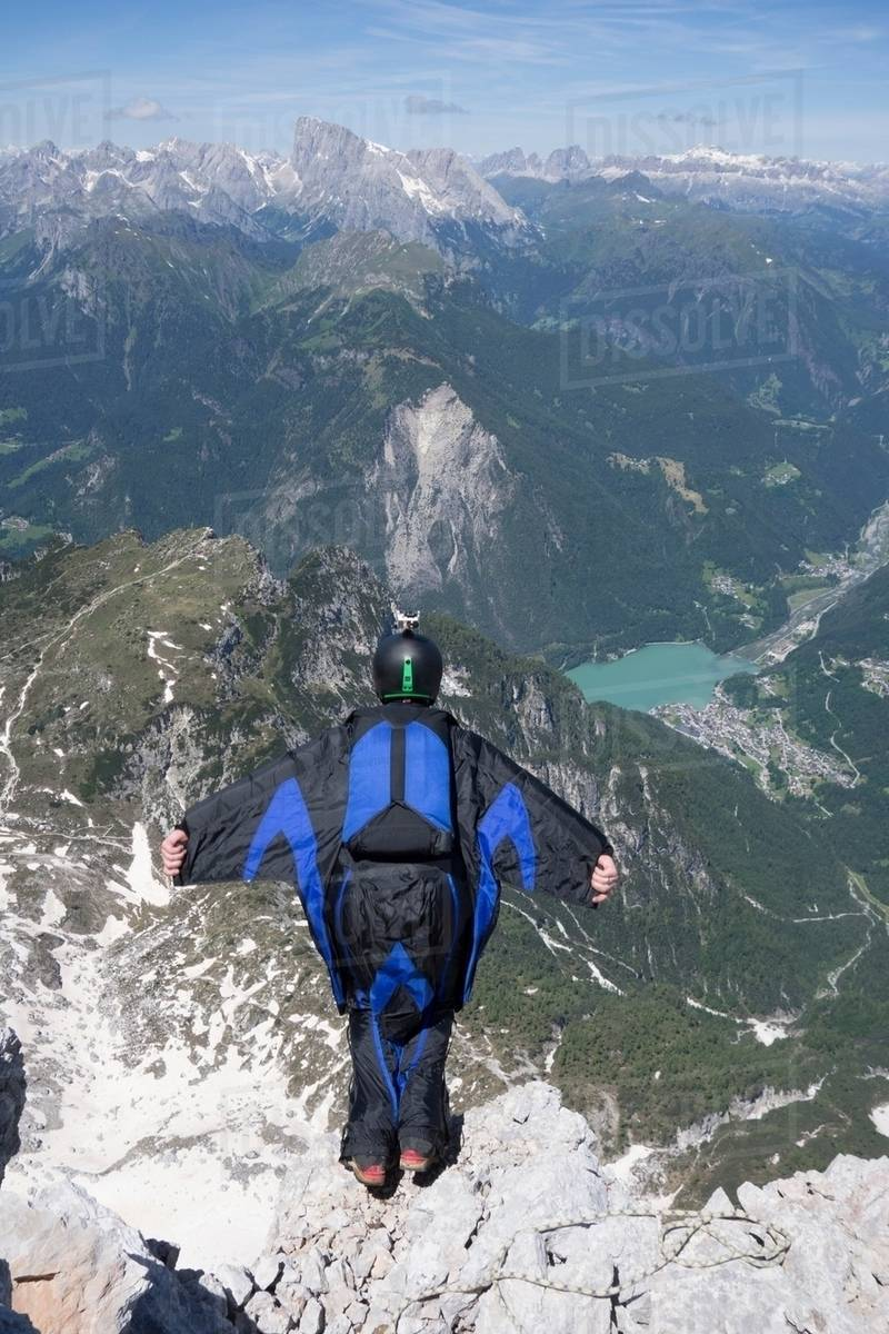 Mid adult man BASE jumping from mountain edge, Alleghe, Dolomites, Italy Royalty-free stock photo