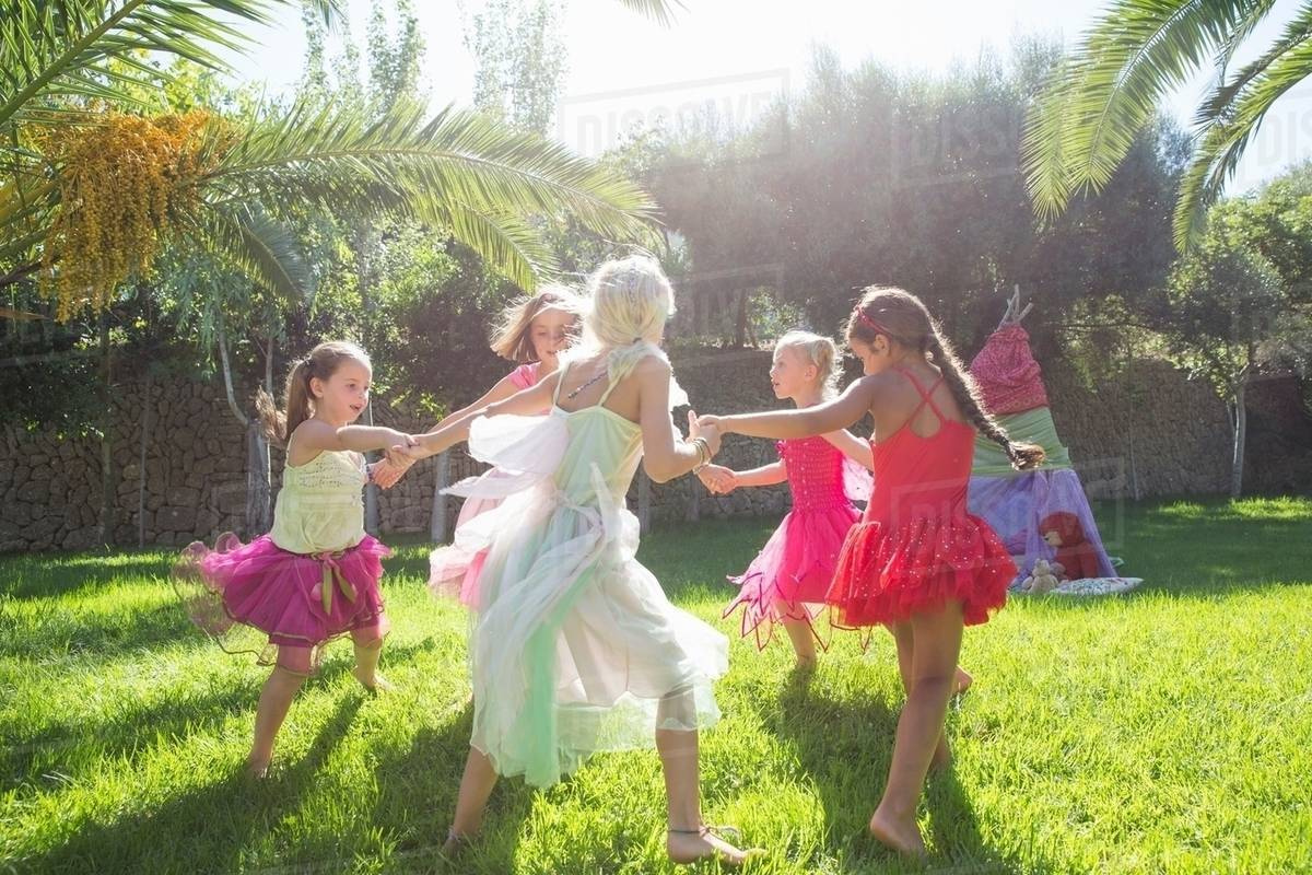 Five energetic girls in fairy costume playing in garden Royalty-free stock photo
