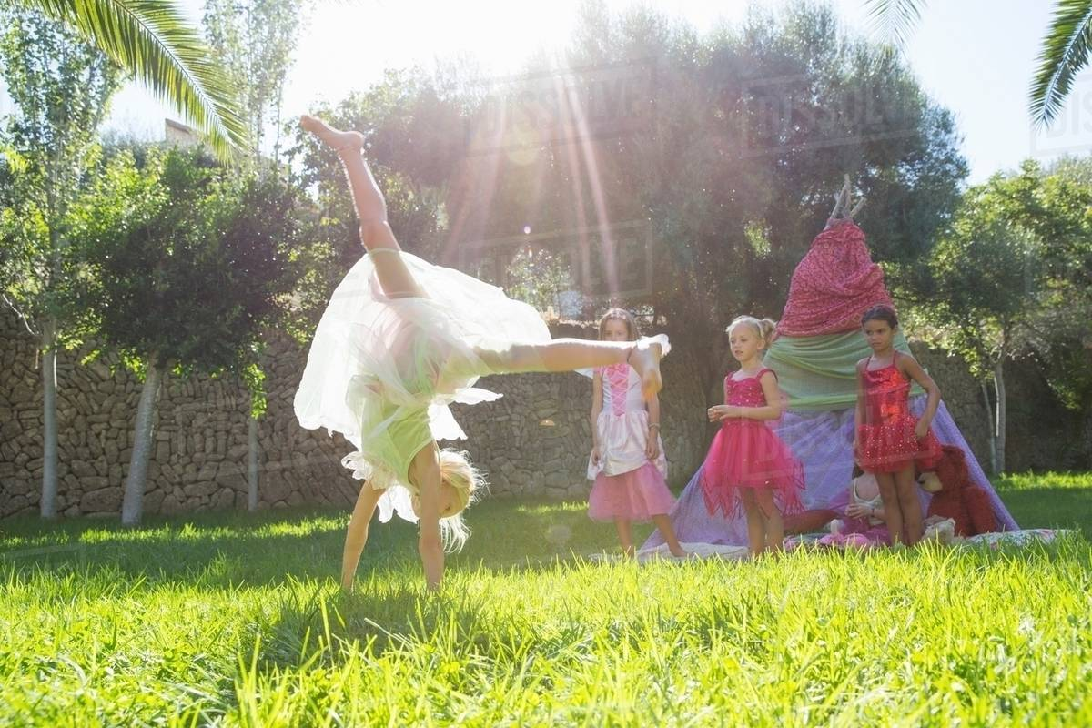 Girls watching friend in fairy costume doing cartwheel in garden Royalty-free stock photo