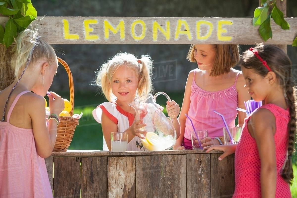 candid portrait of four girls at lemonade stand in park - stock