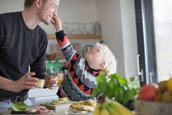 Boy touching father's face in kitchen Royalty-free stock photo