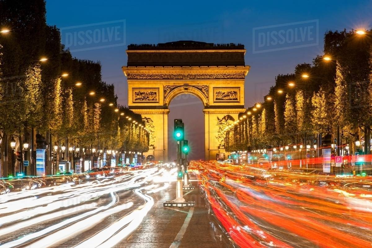 view of the traffic in front of arc de triomphe at night paris