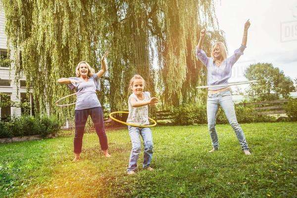 Female members of family playing with hula hoop Royalty-free stock photo