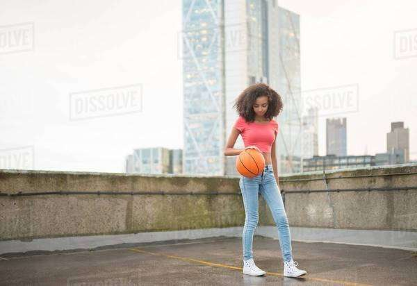 Young woman bouncing basketball Royalty-free stock photo