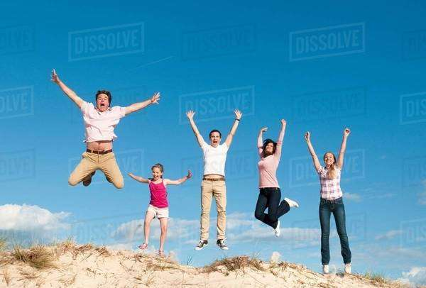 Family cheering together on sand dune Royalty-free stock photo