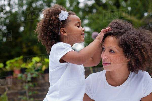 Girl playing with mothers hair outdoors Royalty-free stock photo