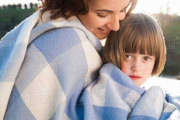 Mother and daughter wrapped in blanket Royalty-free stock photo