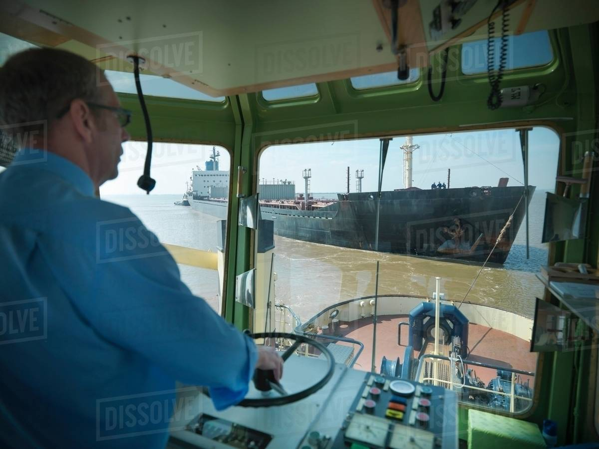 Captain steering in bridge of tugboat towing ship at sea stock photo