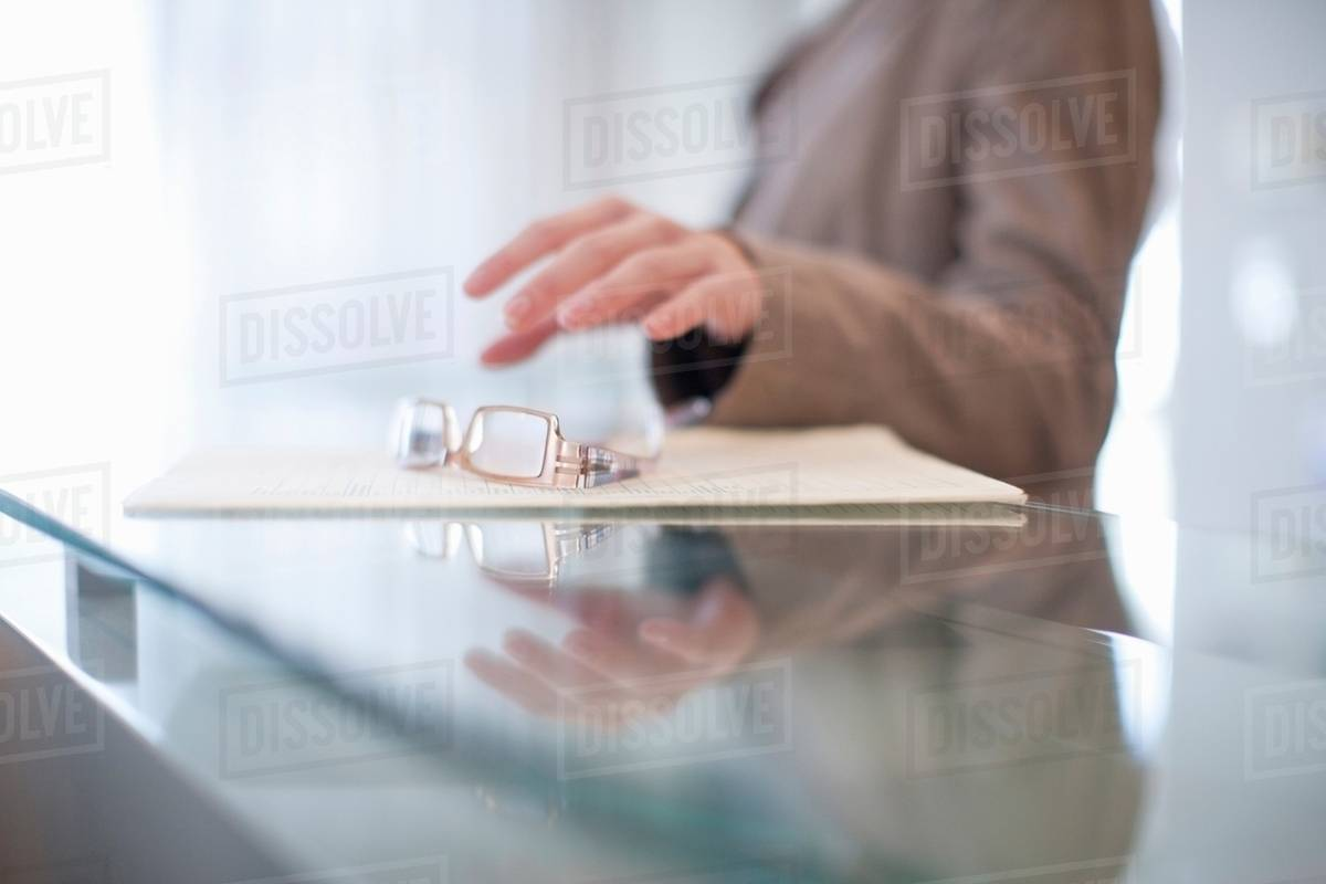 9e367982da Young female picking up eyeglasses from reception desk - Stock Photo ...