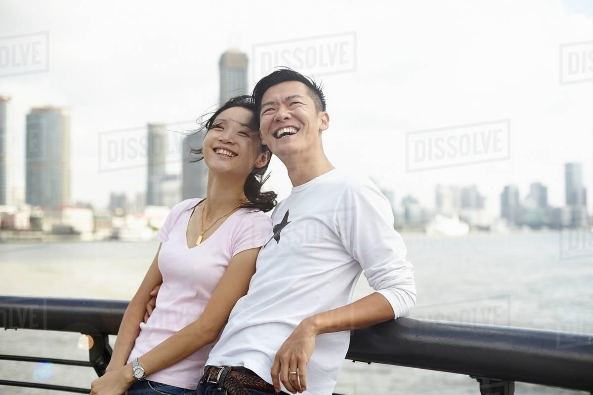 tourist couple leaning against bridge railing looking up the bund