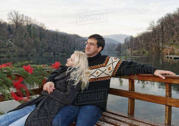 Heterosexual couple relaxing on bench beside lake, Lombardy, Italy Royalty-free stock photo