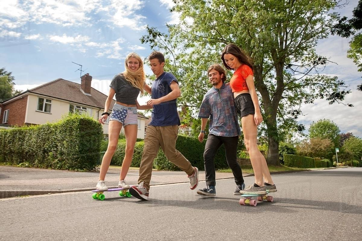 Two young couples skateboarding on road Royalty-free stock photo