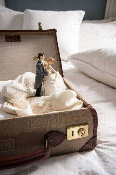 Open suitcase on bed with wedding figurines Royalty-free stock photo