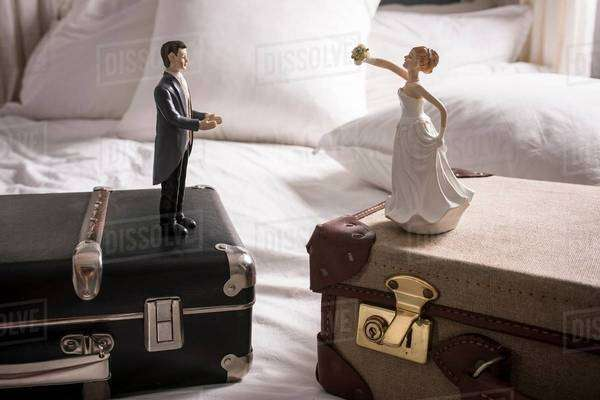 Wedding figurines on separate suitcases Royalty-free stock photo