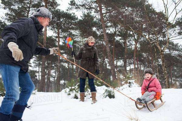 Father and grandmother pulling girl on toboggan in snow Royalty-free stock photo