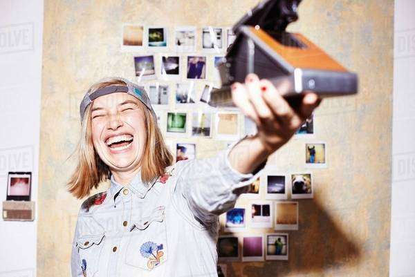 Young woman in front of photo wall taking instant selfie on retro camera Royalty-free stock photo