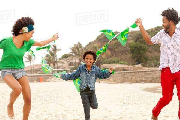 Family playing with string of flags on beach, Rio de Janeiro, Brazil Royalty-free stock photo