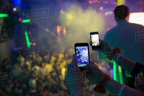 Women taking photograph in nightclub with cellular phone Royalty-free stock photo